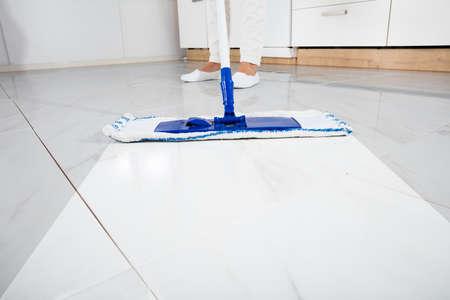 Foto de Low Section Of Person Wiping Floor With Mop In Kitchen Room - Imagen libre de derechos