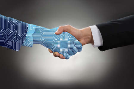 Foto de Close-up Of Digital Generated Human Hand And Business Man Shaking Hands Against Grey Background - Imagen libre de derechos