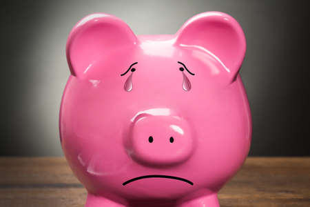 Photo pour Close-up Of A Sad Pink Piggybank Against Grey Background - image libre de droit