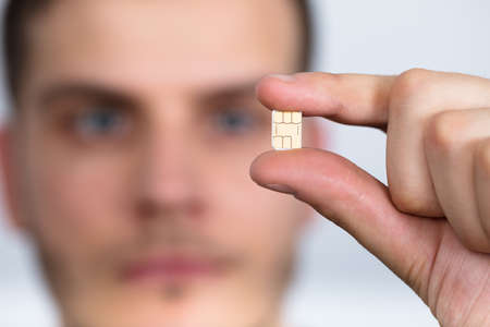 Photo pour Close-up Of A Man Holding Nano Sim Card Between Fingers - image libre de droit