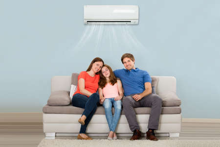 Photo for Happy Family Sitting On Sofa Under Air Conditioning At Home - Royalty Free Image