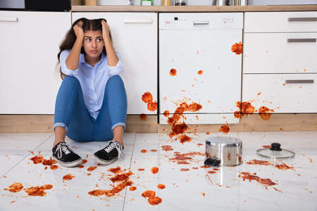 Photo pour Unhappy Woman Sitting On Kitchen Floor With Spilled Food In Kitchen - image libre de droit