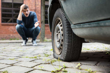 Photo pour Crouched Worried Young Man With Hand On Head Pointing At Punctured Car Tire - image libre de droit