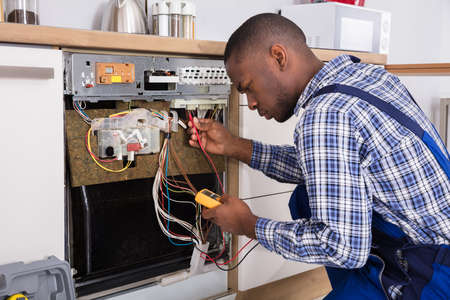 Photo pour Young Male African Technician Fixing Dishwasher With Digital Multimeter In Kitchen - image libre de droit