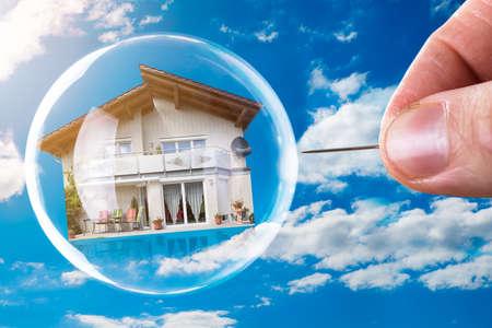 Foto de Human Hand Poking House And Bubble With Needle Against Cloudy Sky - Imagen libre de derechos