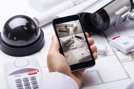 Photo pour Person Hand Using Home Security System On Mobilephone With On Blueprint With Security Equipment - image libre de droit