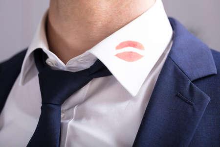Photo pour Close-up Of A Businessman With Lipstick Kiss Marks On Shirt's Collar - image libre de droit