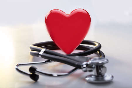 Photo pour Close-up Of A Red Heart With Stethoscope On Desk - image libre de droit