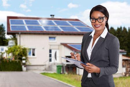 Foto de Portrait Of A Smiling African Businesswoman Filling Document In Front Of House - Imagen libre de derechos