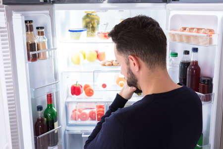 Photo pour Rear View Of A Confused Young Man Looking At Food In Refrigerator - image libre de droit