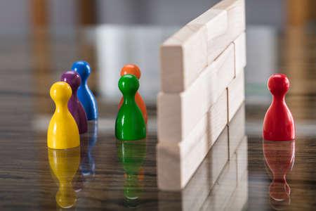 Foto de Close-up Of Red And Blue Figurine Paw Separated By Wooden Blocks On Desk - Imagen libre de derechos