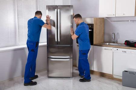 Foto de Two Young Male Movers Placing Steel Refrigerator In Kitchen - Imagen libre de derechos