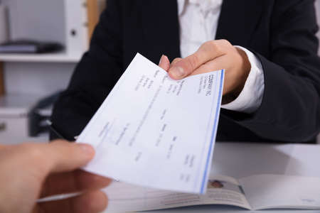 Photo pour Close-up Of A Business Woman Handing Over Cheque To Her Colleague At Workplace - image libre de droit