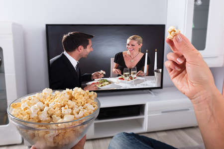 Photo pour Close-up Of A Person's Hand Holding Popcorn While Movie Plays On Television At Home - image libre de droit