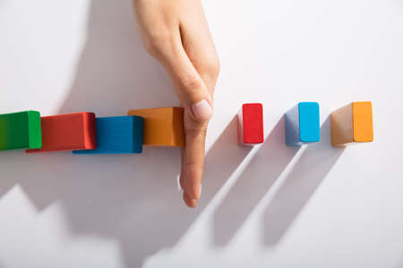 Foto de Close-up Of Businessperson Hand Stopping Colorful Blocks From Falling On Table In Office - Imagen libre de derechos
