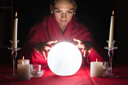 Photo pour Beautiful Young Fortuneteller Holding Hands Around A Glowing Ball - image libre de droit