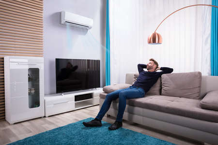 Photo pour Young Man Relaxing On Sofa Near Television At Home - image libre de droit