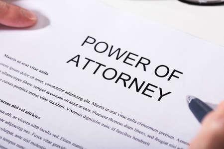 Foto de Close-up Of A Person Holding Pen Over Power Of Attorney Form - Imagen libre de derechos