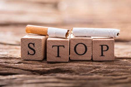 Photo pour Close-up Of A Cigarette And Wooden Blocks Showing Stop Word On Desk - image libre de droit