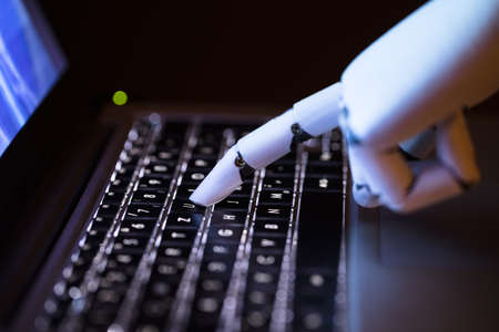 Photo for Close-up Of A Robot's Hand Typing On Laptop - Royalty Free Image