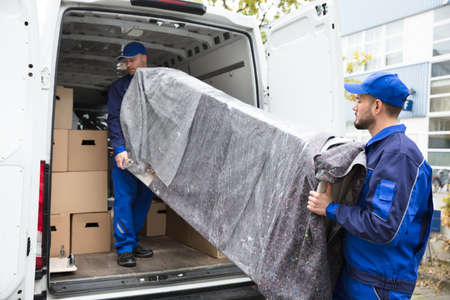 Photo pour Two Young Delivery Men In Uniform Unloading Furniture From Vehicle - image libre de droit