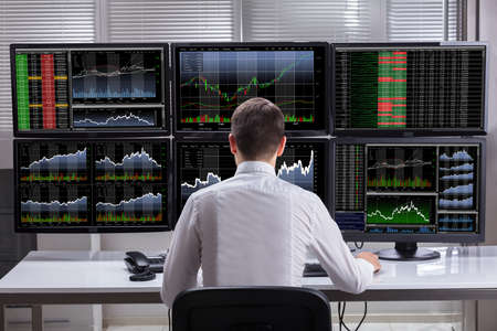 Photo pour Side View Of A Young Male Stock Market Broker Analyzing Graphs On Multiple Computer Screens - image libre de droit