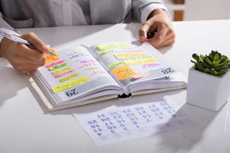 Photo pour Close-up Of A Businesswoman Making Agenda On Personal Organizer At Workplace - image libre de droit