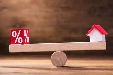 Photo for Balancing Of Percentage Red Block And House Model On The Small Seesaw - Royalty Free Image