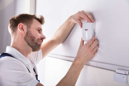 Photo pour Close-up Of Young Male Electrician Installing Security System Door Sensor On Wall - image libre de droit