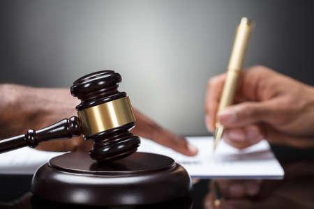 Foto de Close-up Of A Gavel With Person's Hand Signing Legal Document On Wooden Desk - Imagen libre de derechos