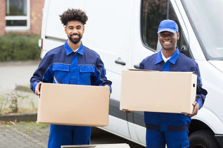 Foto de Close-up Of Two Delivery Men Holding The Cardboard Boxes - Imagen libre de derechos