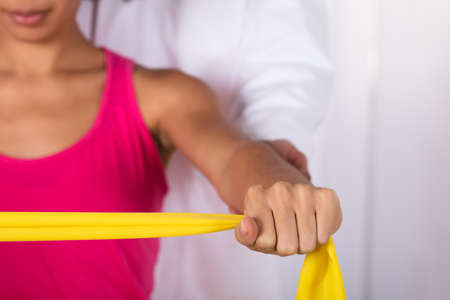 Photo pour Physiotherapist Assisting Woman While Exercising With Exercise Band - image libre de droit