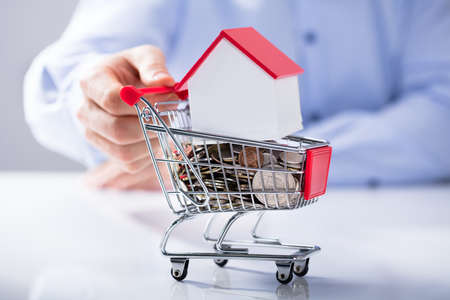Photo for Man's Hand Holding Shopping Cart Filled With Coins And House Model On The White Desk - Royalty Free Image