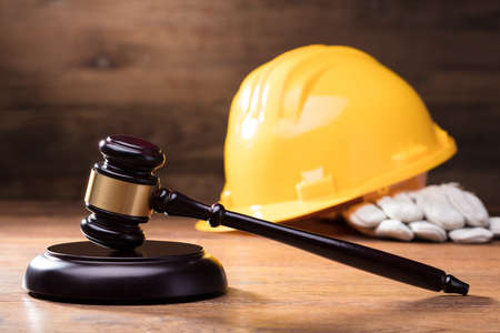 Photo pour Judge Gavel In Front Of Yellow Safety Helmet On The Wooden Table - image libre de droit