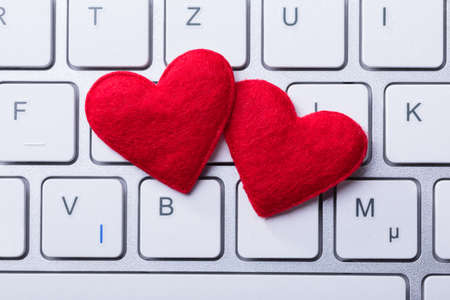 Foto de Elevated View Of Soft Two Red Hearts Shape On Keyboard - Imagen libre de derechos