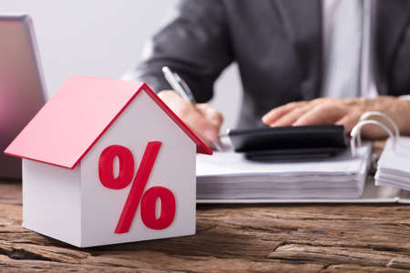 Photo pour Close-up Of A House Model With Percentage Symbol And Red Roof On Wooden Desk - image libre de droit
