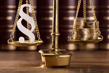 Close-up Of White Paragraph Symbol And Stacked Golden Coins On Justice Scale
