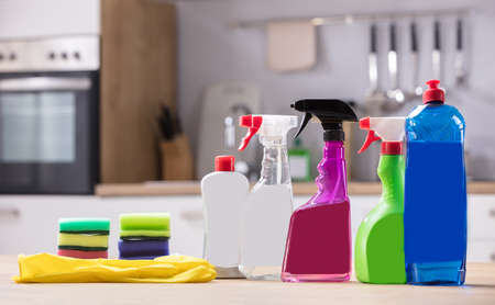 Photo pour Close-up Of Cleaning Equipments And Gloves On Wooden Desk - image libre de droit