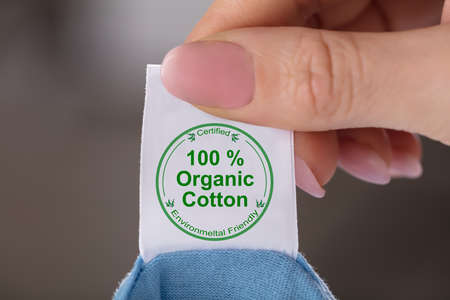 Foto de Close-up Of A Person's Hand Holding Label Showing 100 Percent Organic Cotton - Imagen libre de derechos