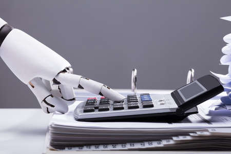 Photo pour Close-up Of A Robotic Hand Calculating Bills Using Calculator In Office - image libre de droit
