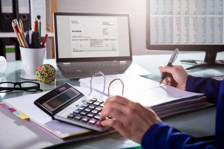 Photo pour Close-up Of A Businessperson's Hand Calculating Invoice At Workplace - image libre de droit