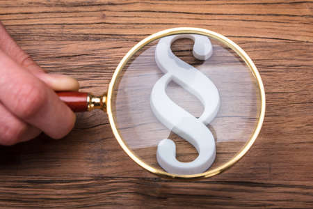 Photo for Businessperson's Hand Holding Magnifying Glass Over Paragraph Symbol On Wooden Desk - Royalty Free Image