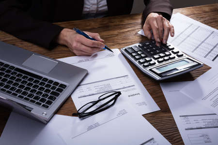 Photo pour Businessperson Calculating Invoice With Calculator In Office - image libre de droit