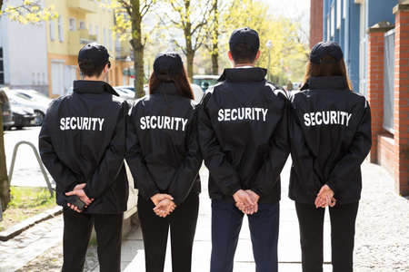 Photo pour Rear View Of Security Guards With Hands Behind Back Standing In A Row - image libre de droit
