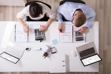 Photo pour Two Young Businesspeople Calculating Invoice With Calculator - image libre de droit