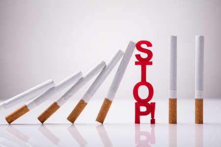 Photo pour Falling Cigarettes Stopped By Stop Word Against White Background - image libre de droit