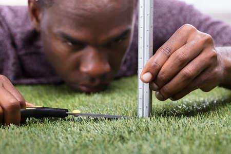 Foto de Close-up Of A Man Cutting Green Grass Measured With Ruler - Imagen libre de derechos