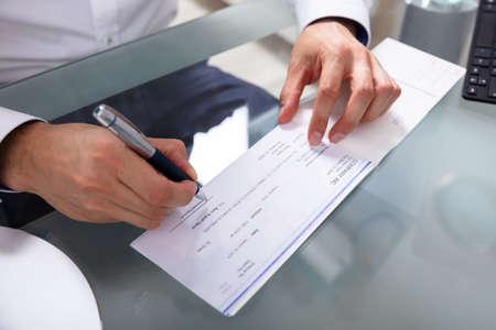 Photo pour Businessman's Hand Signing Cheque On Glass Desk - image libre de droit
