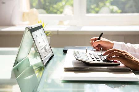 Photo pour Close-up of a businessman's hand calculating invoice using calculator - image libre de droit