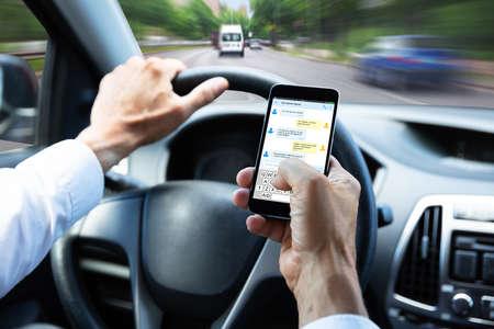 Foto de Close-up Of A Man's Hand Typing Text Message On Mobile Phone While Driving Car - Imagen libre de derechos